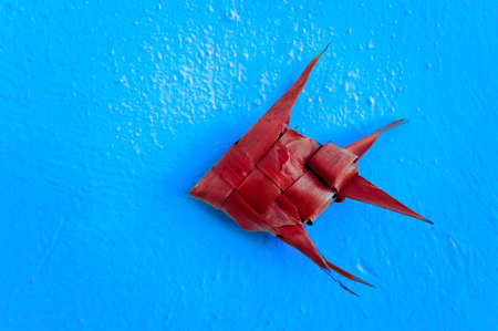 Close up of an origami fish hanging on the wall