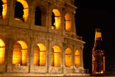 ROME  August 18, 2012  An empty beer bottle on the background of the Colosseum in Rome, as a concept of fun in the Roman nights.