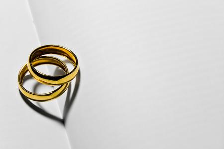 후계자의 그림자에서 두 개의 하트를 만드는 두 개의 결혼 반지를 닫습니다.