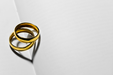 Close up of two wedding rings that create two hearts in heir shadow
