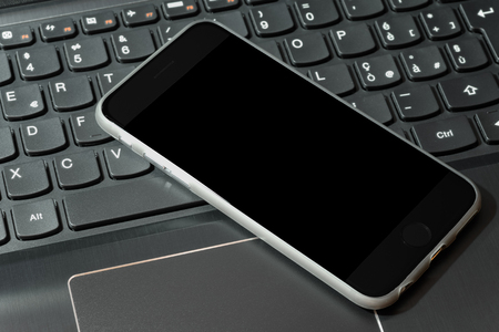 Smartphone on top of laptop as a concept of technology Stock Photo
