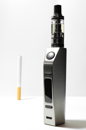 A conceptual composition between traditional cigarette and electronic cigarette. Stock Photo