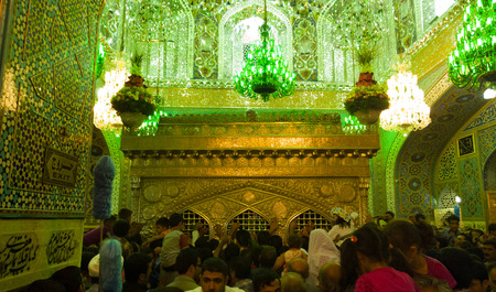 imam: Picture of Interior of the shrine of Imam Ali bin Mussa Al-rida, And shows a golden shrine decorated with Islamic motifs and verses, And the number of visitors roam around the shrine.