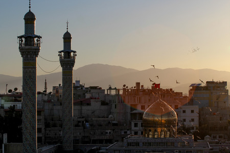 damascus: External shot for Sayeda Zeinab shrine in Damascus capital of Syria, which showing the shrine with one golden dome and two minarets and some Residential buildings. Editorial