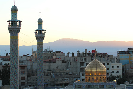damascus: External shot for Sayeda Zeinab shrine in Damascus capital of Syria which showing the shrine with one golden dome and two minarets and some Residential buildings.