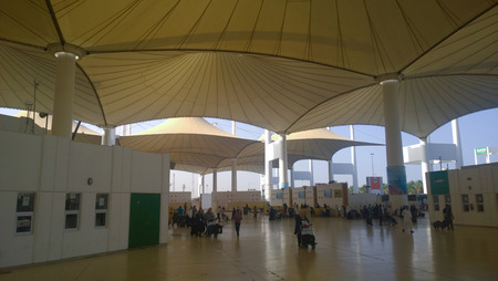 competent: Picture of the entrance to King Faisal Airport in Jeddah in Saudi Arabia, and appear in the image giant umbrellas and    some buildings competent to serve passengers, and this Airport is to receive the pilgrims only.