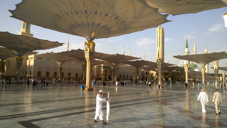 minarets: An external image of the Prophets Mosque in Medina in Saudi Arabia, Show It shows umbrellas which protects from the sun and the minarets of the mosque.