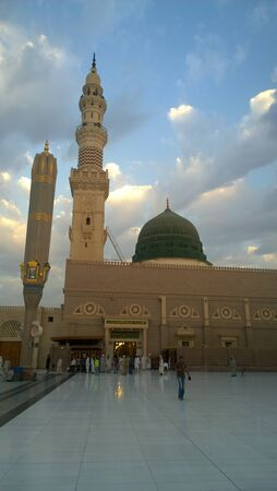 sliver: An external image of the Prophets Mosque in Medina in Saudi Arabia,  It shows the minarets and green dome and sliver dome of the mosque.