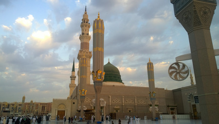 minarets: An external image of the Prophets Mosque in Medina in Saudi Arabia,  It shows the minarets and green dome and sliver dome of the mosque.