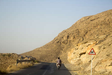 frequented: two men ride byic on road in akhlmend ,which is Beautiful tourist area containing waterfalls, mountains and plateaus, It is close to the city of Mashhad in Iran. Frequented by a lot of tourists during their visit to Iran.