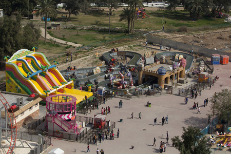 dream land: picture for Iraqi kids riding some games in  Zawraa park in Baghdad city capital of Iraq. Editorial