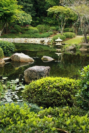 garden pond: neat Japanese style garden with calm pond and typical lantern at a pond Stock Photo