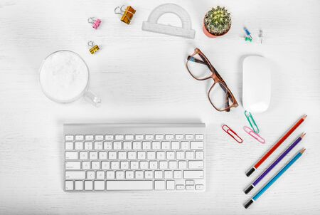 White office desk table with computer mouse and keyboard, cup of latte coffee, pencils and eye glasses. Top view with copy space, flat lay. 스톡 콘텐츠