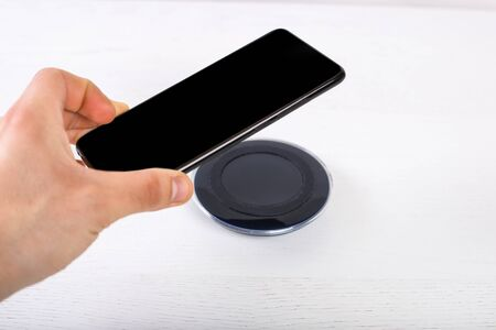 Hand putting mobile phone on wireless charger, modern equipment on white background Фото со стока - 132044703