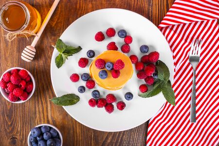 Top view of appetizing pancakes with honey, raspberries and blueberries on a wooden background. Beautiful American pancakes Stok Fotoğraf