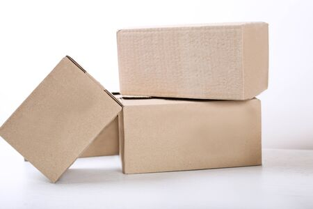 Moving in. Stack of cardboard boxes on white background. Close up