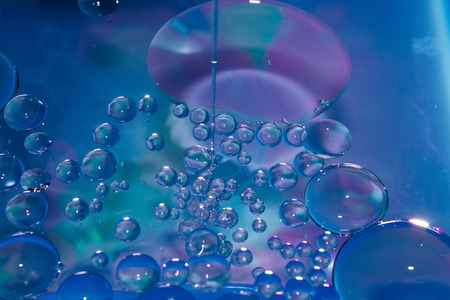 Misted glass, blue and purple rain drops dew drops on colorful abstract cool color background condensation on tinted vibrant glass window