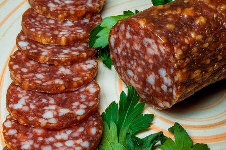 salame: Smoked sausage salami sliced on a plate with greens. Stock Photo