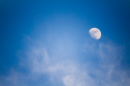 A big moon in the afternoon against a blue sky with clouds.