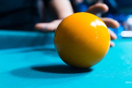 Billiard ball on the field in hand.