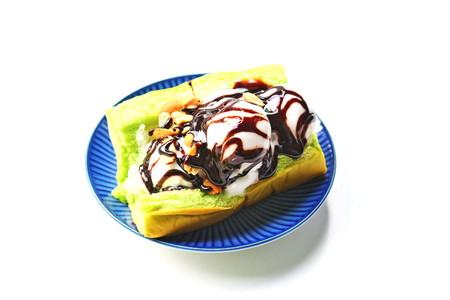 Coconut ice creams on pandan leaf bread with chocolate and roasted peanuts on top set on blue dish, thai style ice cream.