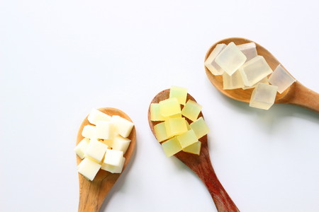 Three kinds of soap bases, white, yellow cocoon, and transparent on wooden paddle on white background with copy space.