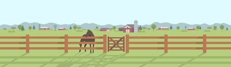 Horse standing behind the wooden fence at pasture land with houses and trees in the distance