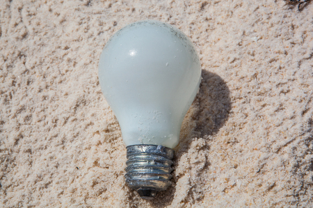 inclement: incandescent light bulb in the sand Stock Photo