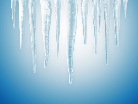 winter thaw: Icicles on blue background