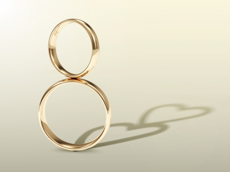 Golden Wedding Rings with shadows in shape of heart  photo