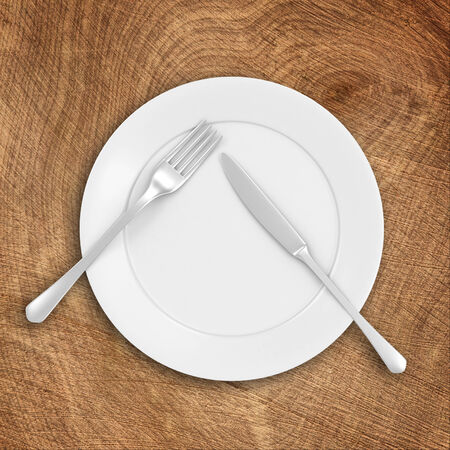 silver ware: White Plate with Fork and Knife on Wooden Table Stock Photo