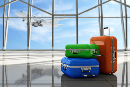 Traveler Suitcases in Airport Terminal Waiting Area. Empty Hall Interior with Large Windows and Flying Airplane behind. Focus on Suitcases. Vacation Concept.