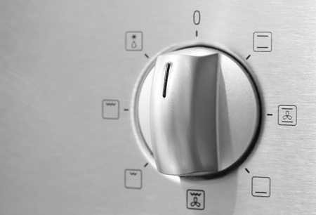 Metallic Toggle Switch of Cooker Oven. Close-up View photo