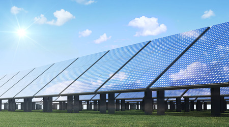 Alternative Energy Concept. Modern Solar Panels Farm on beautiful Green Grass with Sunshine and Clouds Stock Photo