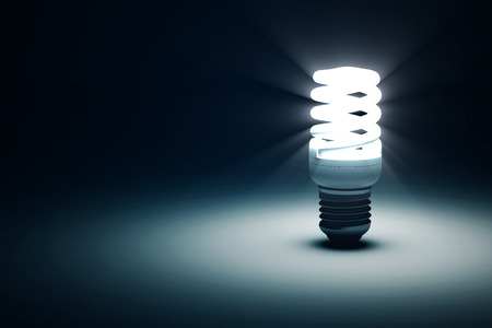 light rays: Illuminated Fluorescent Light Bulb on blue dark background with place for Your Text