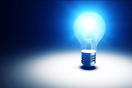 metal light bulb icon: Illuminated Light Bulb on blue dark background with place for Your Text Stock Photo