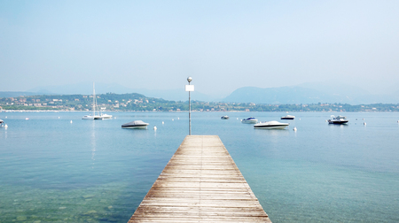 Wooden Pier in the middle of the Beautiful Garda Lake Scenery, Italy.