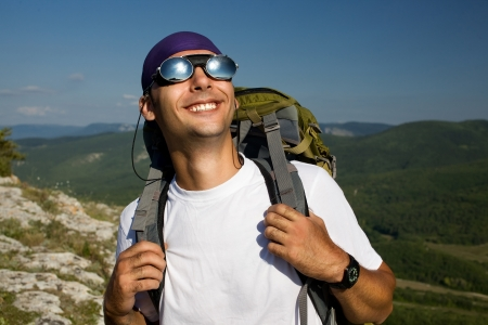 Tourist male looking on the sun and smilling  Mirror sunglasses, white t-shirt, green rucksack  Close up  Top of mountains