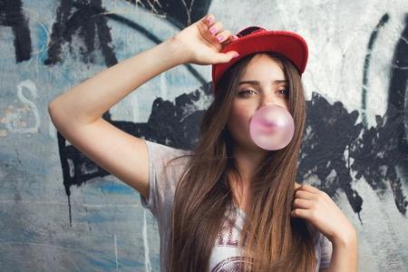 cool girl: trendy beautiful long haired model posing on graffiti background  Blow bubblegum  red cap  grey t-shirt
