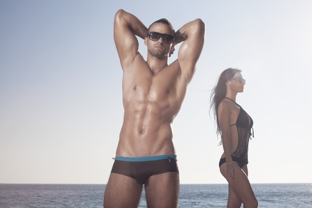 Sporty guy showing his perfect oiled body. Girl behind photo