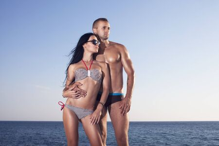 Two perfect bodies person posing on sea background. Male and famale. Reklamní fotografie - 26444322