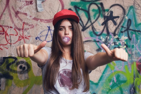 gums: trendy beautiful long haired model posing on graffiti background. Blow bubblegum and show thumb up. red cap. grey t-shirt.