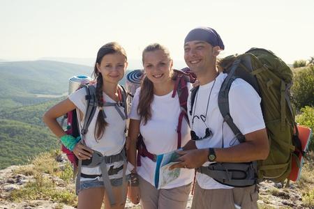 Groep van toeristen in de bergen Twee jonge vrouwen en man ontdekken kaart Stockfoto