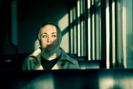 genre: Genre portrait of lonely woman in train car. headscarf. beige coat