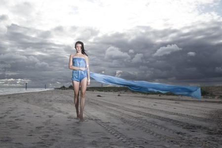 Pretty model holding long blue dress on the beach. Windy and cloudy summer weather photo