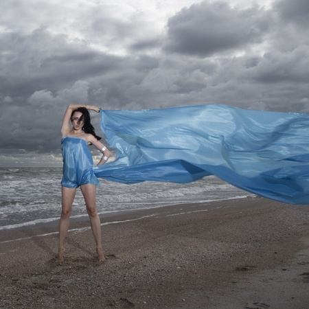 Brunete model standing on sea shore with long flag material photo
