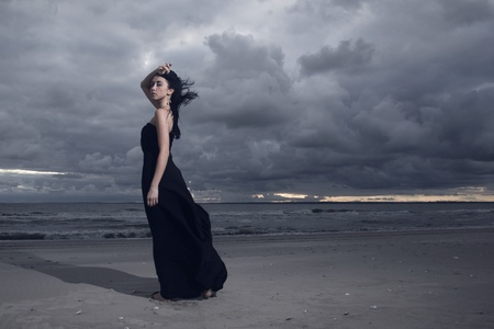 Beautiful brunete model in long black dress standing on the beach. Cloudy weather. Sunset photo