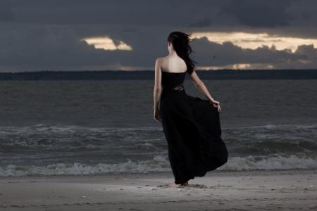 Alone brunete model holding her long black dress photo