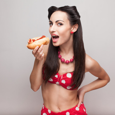 Sexy pinup model eating fast food sandwich photo