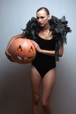 Fashionable female model holding halloweens pumpkin. Studio shot photo